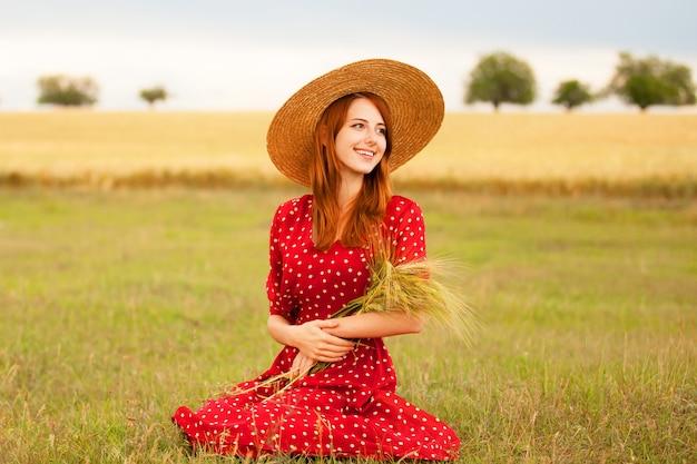 Roodharige meisje in een rode jurk aan het tarweveld Premium Foto