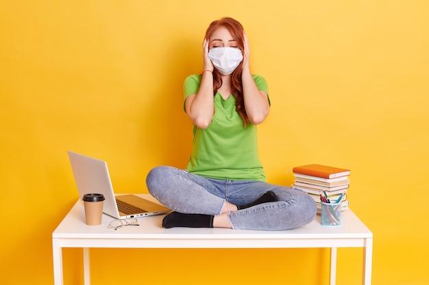 Roodharige meisje in medische masker zit met gekruiste benen op witte tafel, bedekt haar oren met handpalmen en houdt de ogen gesloten, het dragen van spijkerbroek en t-shirt, omringd met laptop, koffie, pennen Gratis Foto
