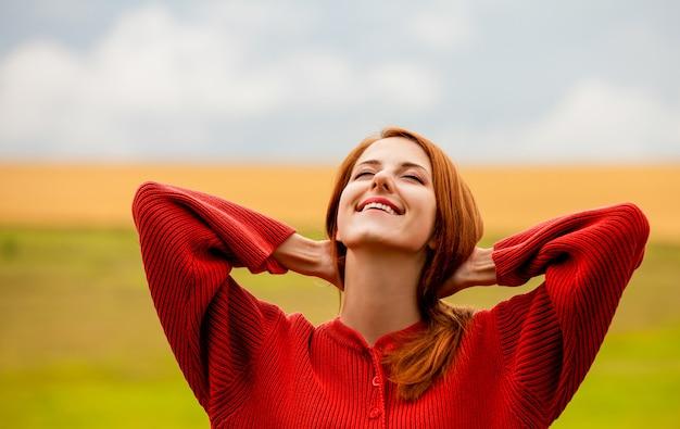 Roodharige meisje op weide in de buurt van tarweveld Premium Foto
