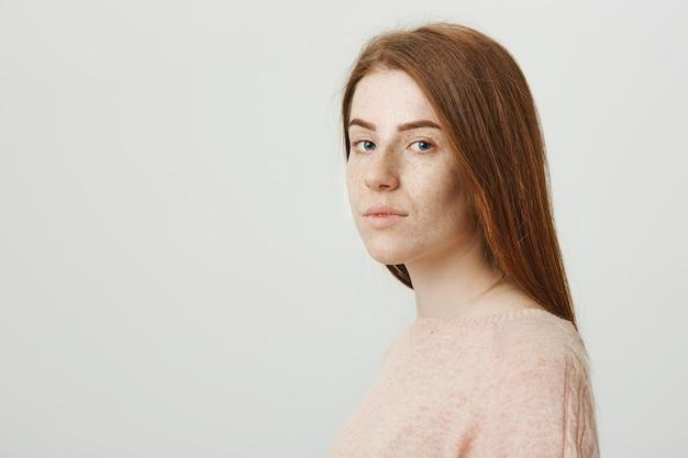 Roodharige mooi meisje draai gezicht naar de camera, kijkend serieus Gratis Foto