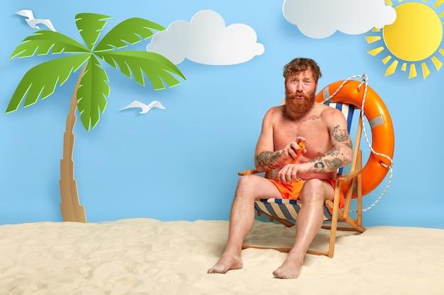 Roodharige poseren op het strand met zonnebrandcrème Gratis Foto
