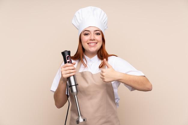 Roodharige tiener meisje met behulp van staafmixer over met duimen omhoog omdat er iets goeds is gebeurd Premium Foto