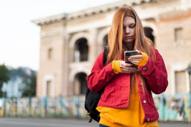 Roodharige vrouw die haar telefoon controleert Premium Foto