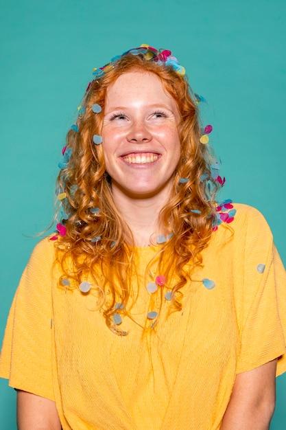 Roodharige vrouw feesten met confetti in haar haar Gratis Foto