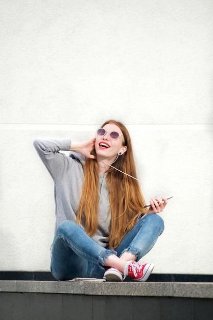 Roodharige vrouw gekleed in hoody, jeans en rode sneakers, met rode lippenstift geschilderde lippen luisteren naar muziek in smartphone in zonnige zomerdag en plezier Premium Foto