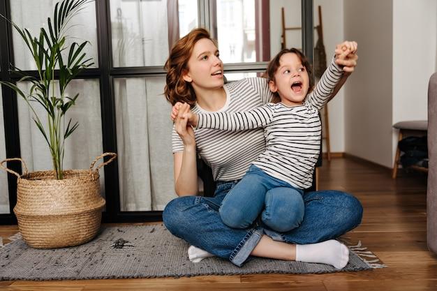 Roodharige vrouw in gestreept t-shirt knuffelt haar dochter en speelt met haar zittend op de vloer in de woonkamer. Gratis Foto