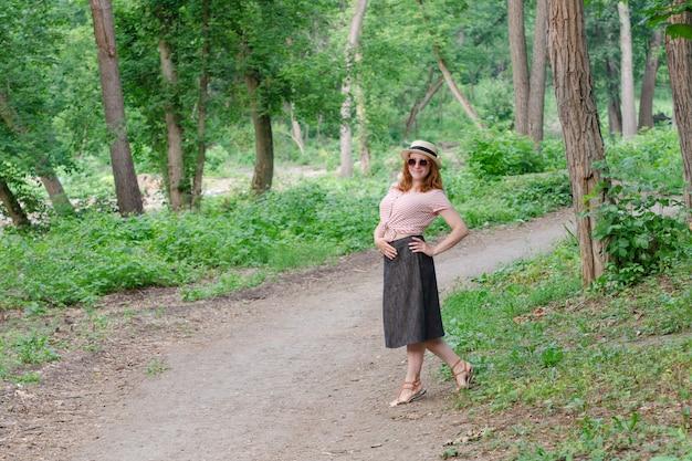 Roodharige vrouw in hoed poseren op pad tegen het groene bos Premium Foto