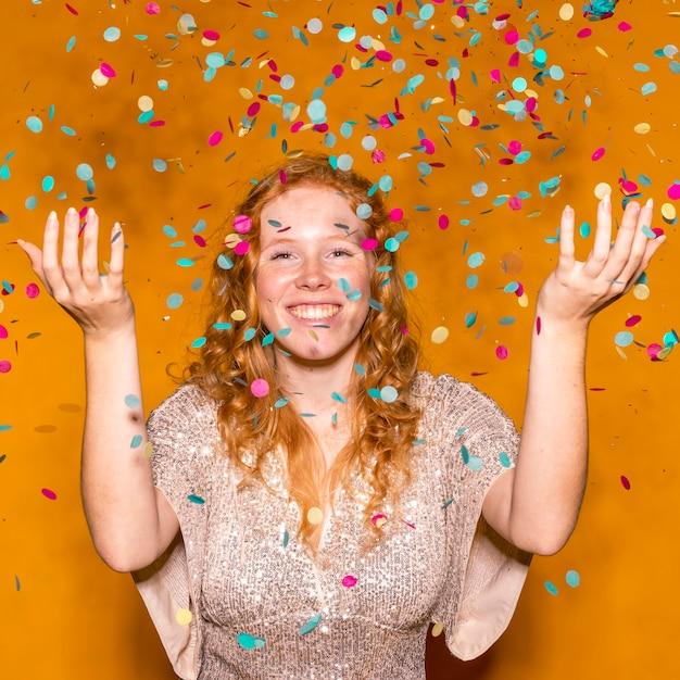 Roodharige vrouw kleurrijke confetti gooien Gratis Foto