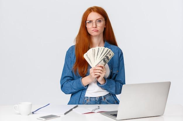 Roodharige vrouw met bankbiljettenventilator Premium Foto