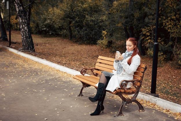 Roodharige vrouw van middelbare leeftijd met een smartphone in haar hand zit op een bankje in het park Premium Foto