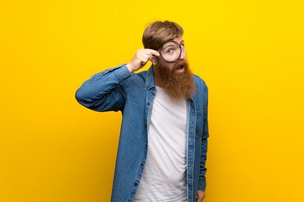 Roodharigemens met lange baard over geïsoleerde gele muur die een vergrootglas houden Premium Foto