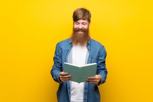 Roodharigemens met lange baard over geïsoleerde gele muur die en een boek houden lezen Premium Foto