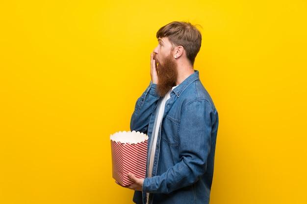 Roodharigemens met lange baard over gele muur die een kom popcorns houden Premium Foto