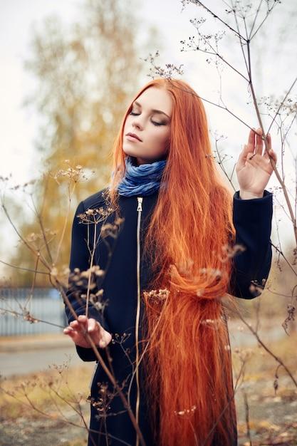 Roodharigevrouw die in de herfst de stad lopen. koude Premium Foto