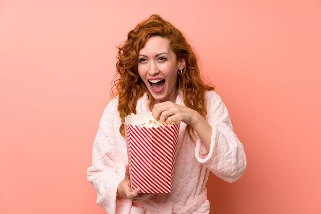 Roodharigevrouw die in peignoir popcorns eten Premium Foto