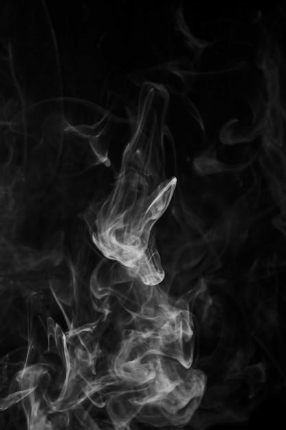 Rookbeweging over zwarte achtergrond met exemplaarruimte voor het schrijven van de tekst Gratis Foto