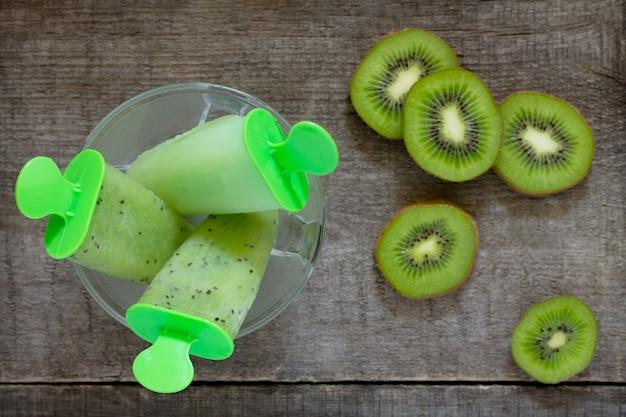 Roomijs met kiwi en fruitijs tegen een uitstekende houten achtergrond, exemplaarruimte. het concept van een gezond dieet en detoxdieet. Premium Foto