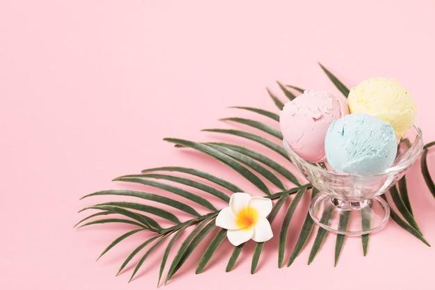 Roomijsballen op glaskom dichtbij installatiegebladerte en bloem Gratis Foto