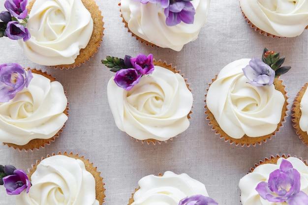 Rose flower frosting vanille cupcakes met paarse eetbare bloemen Premium Foto
