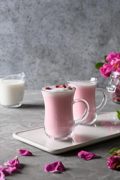 Rose moon melk in glazen bekers en vallende rozenblaadjes op grijze achtergrond. detailopname. verticaal formaat. Premium Foto