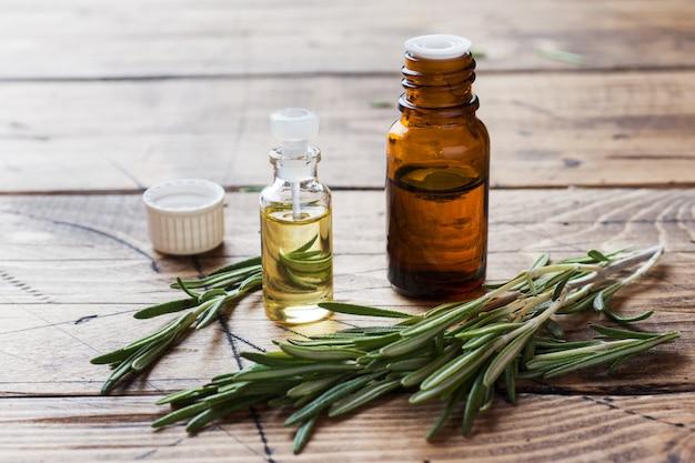 Rosemary etherische olie in een glazen fles met verse tak rozemarijn kruid Premium Foto