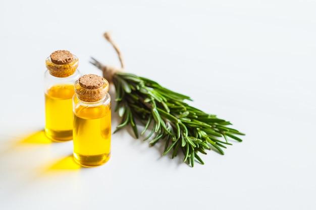 Rosemary etherische olie in glasflessen, witte achtergrond, exemplaarruimte. Premium Foto