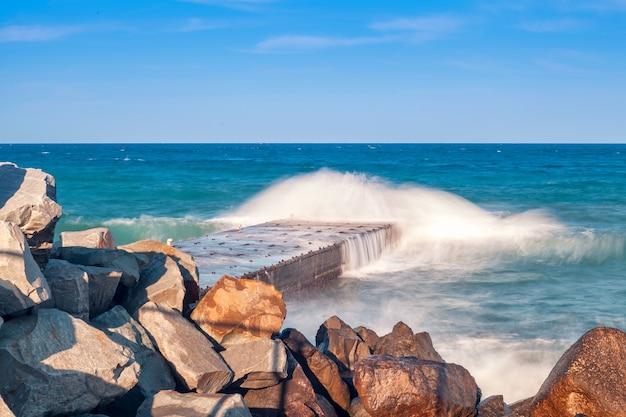 Rotsachtige kust in zonnige dag. golven slaan tegen over golfbrekers en pier. prachtig natuurzeegezicht in de zomer. Premium Foto