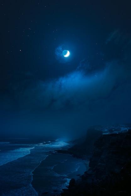 Rotsachtige kust onder volle maan Gratis Foto