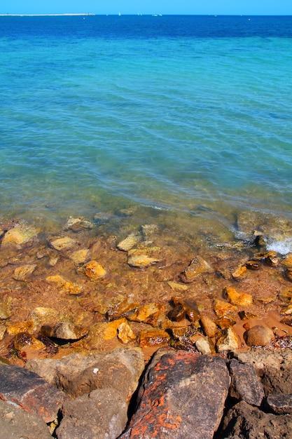 Rotsachtige strandkust turkooise oceaanoverzees Premium Foto