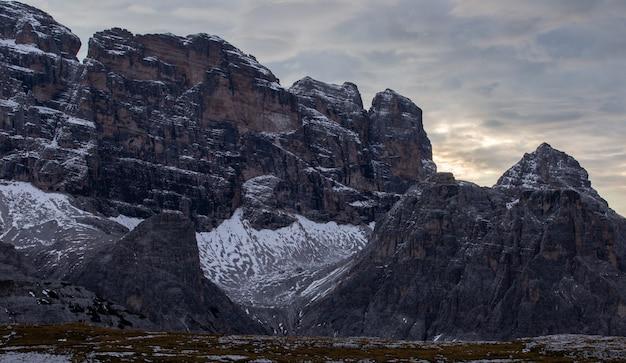 Rotsen in de italiaanse alpen onder de donkere bewolkte avondhemel Gratis Foto