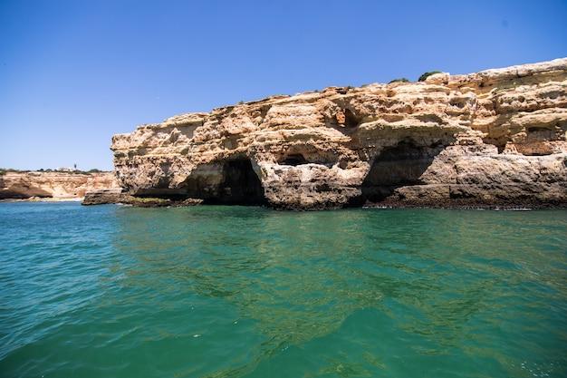 Rotsen, kliffen en oceaanlandschap aan de kust in aalgarve, portugal uitzicht vanaf de boot Gratis Foto