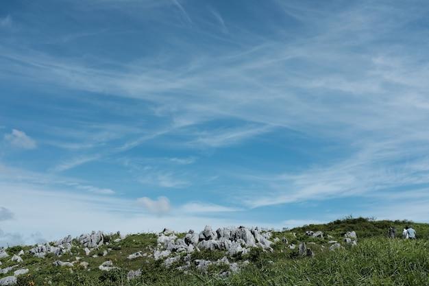 Rotsen op een heuvel bedekt met gras onder een blauwe hemel Gratis Foto