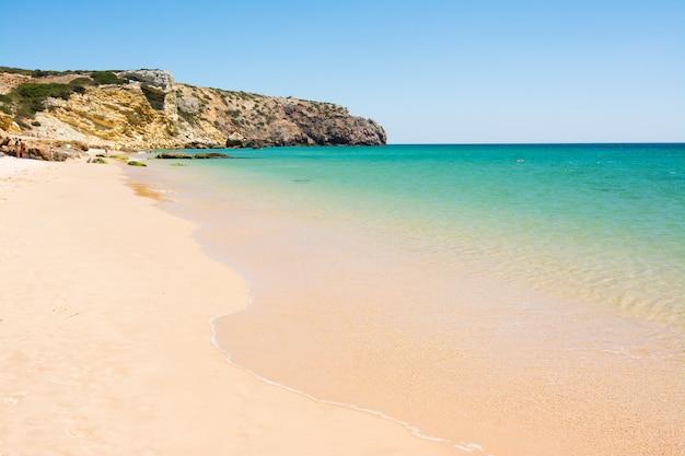 Rotsen op het zandstrand van praia do amado, portugal Premium Foto