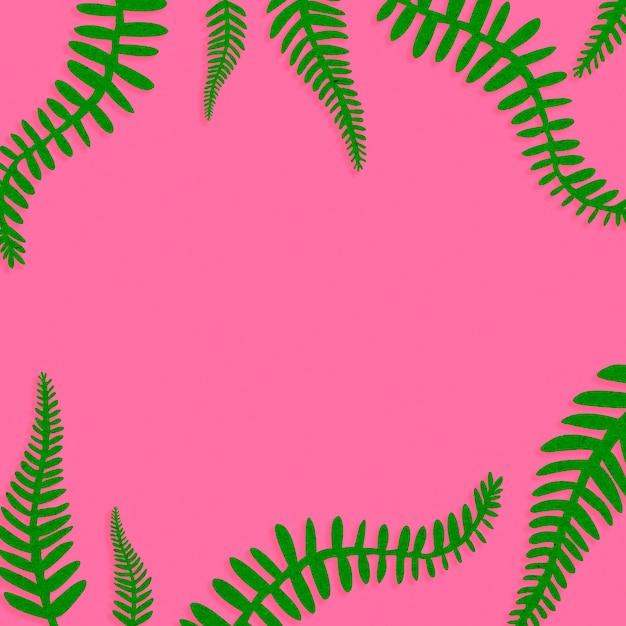 Roze achtergrond met groene bladeren Gratis Foto
