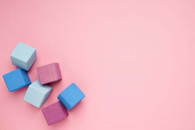 Roze achtergrond met kleurrijke houten kubussen. creativiteit speelgoed. bouwstenen voor kinderen. Premium Foto