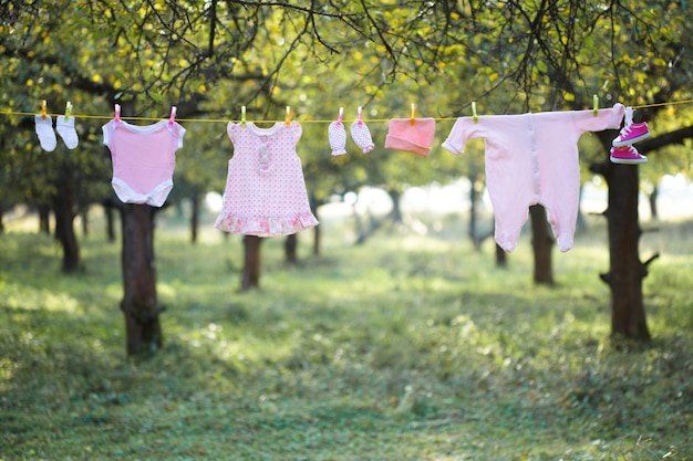 Roze babykleding buiten in de tuin Premium Foto