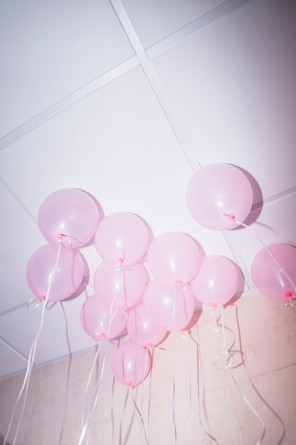 Roze ballonnen drijvend op het plafond van een feestje Gratis Foto