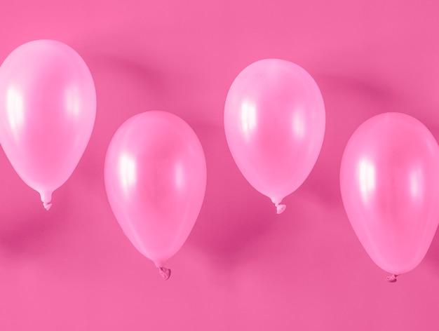 Roze ballonnen op roze achtergrond Gratis Foto