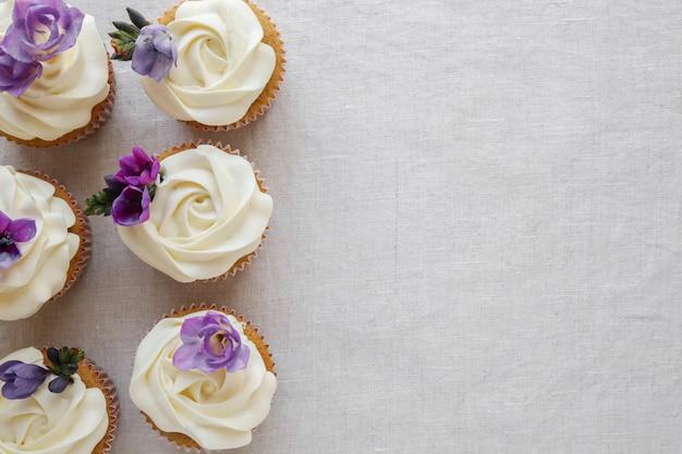 Roze bloem glazuur vanille cupcakes met paarse eetbare bloemen Premium Foto