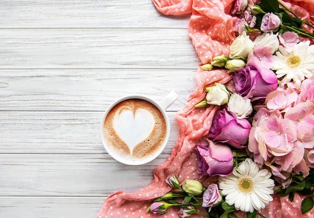 Roze bloemen en kopje koffie op een witte houten achtergrond Premium Foto
