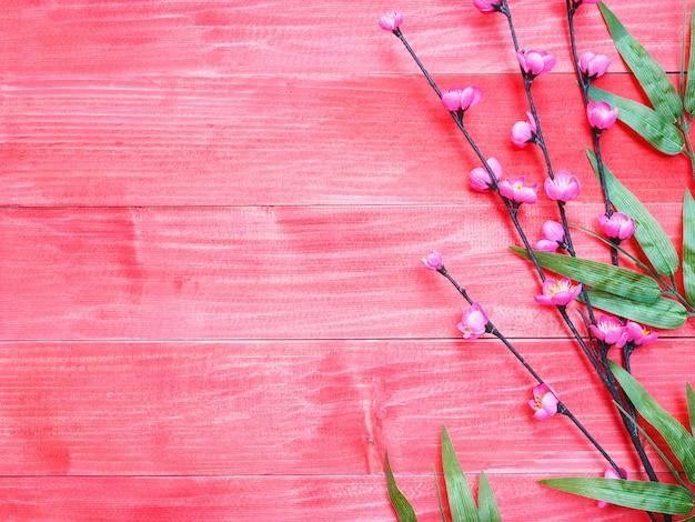 Roze bloesembloemen en groene bamboebladeren op rode houten achtergrond Premium Foto