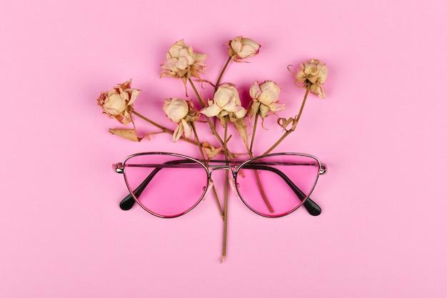 Roze bril in kleuren. plat lag. glamour en stijl. brillen voor dames. roze bril op een roze achtergrond versierd met gedroogde rozen. Premium Foto