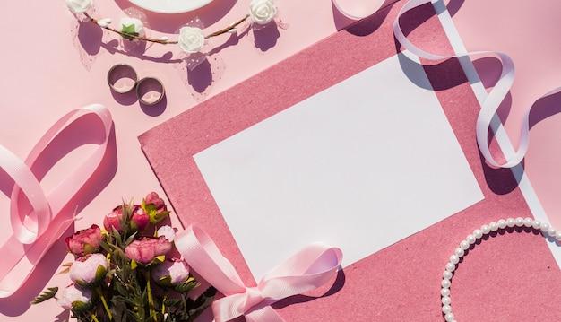 Roze bruiloft uitnodiging naast bruiloft items Gratis Foto