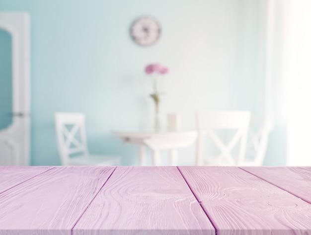 Roze bureau op de voorgrond met onduidelijk beeldeettafel op de achtergrond Gratis Foto