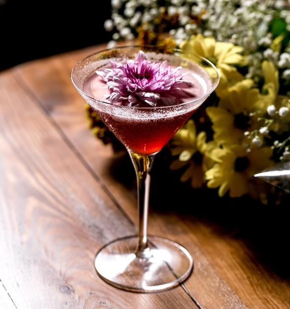 Roze cocktail gegarneerd met bloem in martiniglas Gratis Foto
