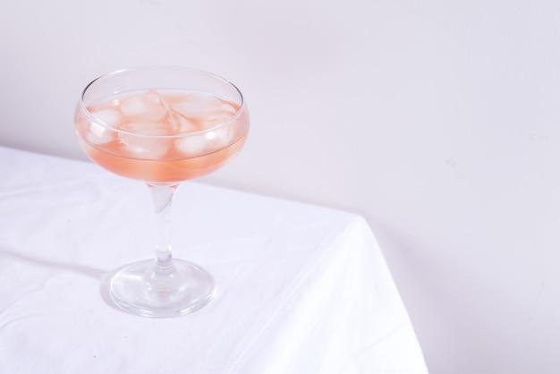 Roze cocktail met rozemarijn en ijs in glas op een wit tafelkleed op de lijst Premium Foto