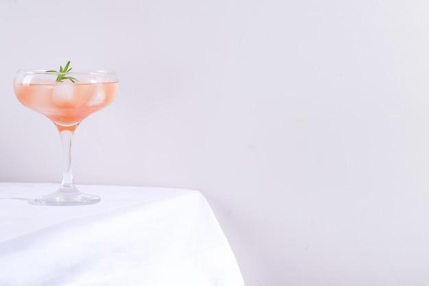 Roze cocktail met rozemarijn en ijs in glas op een wit tafelkleed op de lijstachtergrond Premium Foto