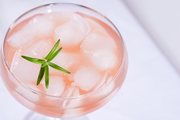 Roze cocktail met rozemarijn en ijs op een wit tafelkleedclose-up Premium Foto