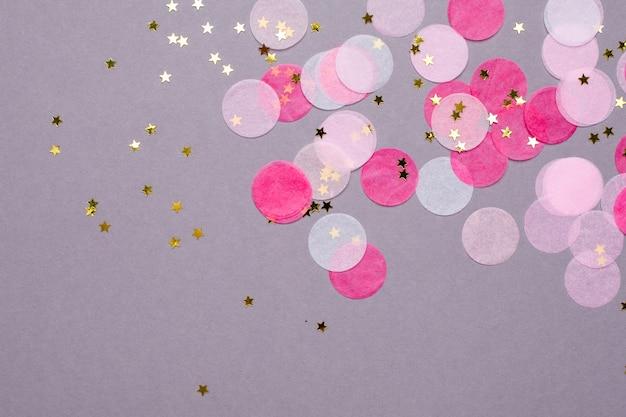 Roze confetti met gouden sterren op grijs met copyspace Premium Foto