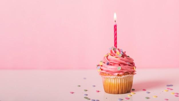 Roze cupcake met aangestoken kaars Gratis Foto